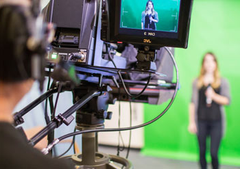 Student being filmed in front of a green screen
