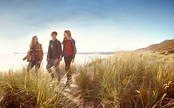 Three students walking through sand dunes on warm clo日es at dusk