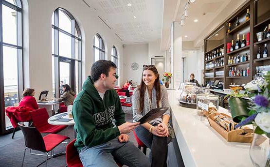 Two students enjoying a coffee at GH Cafe in the Great Hall on Bay Campus