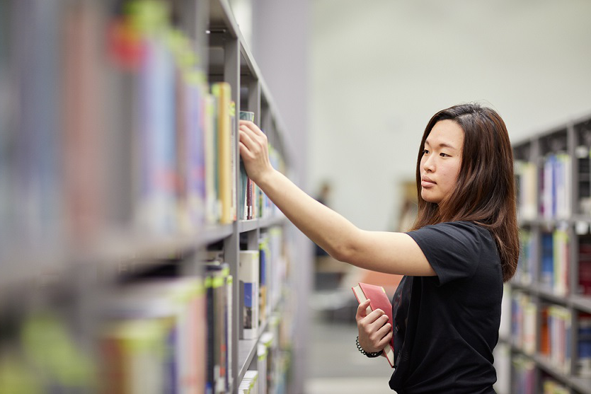 Female student selecting a book in Bay Campus Library