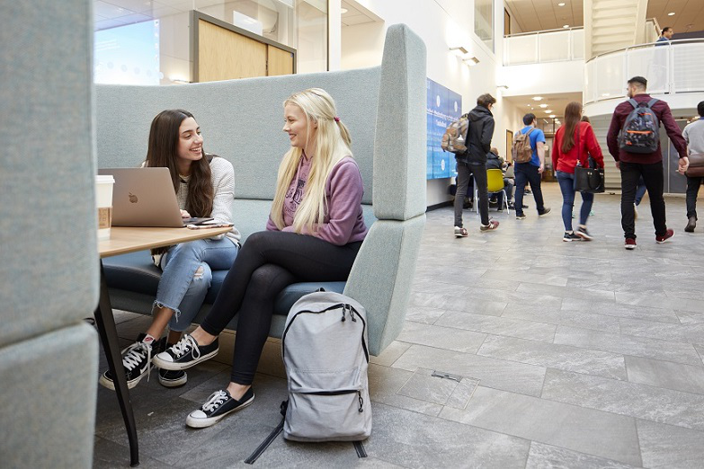 Two students sat chatting in the Bay Campus library