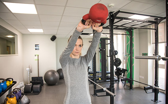 A woman swings a kettlebell above her head