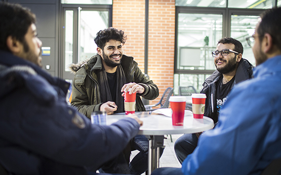 Students drinking coffee around a table