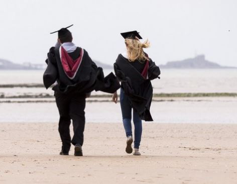Graduated students walking on the beach