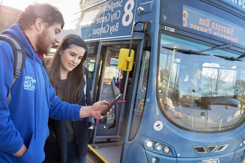 Two students standing next to the number 8 bus looking at their phone
