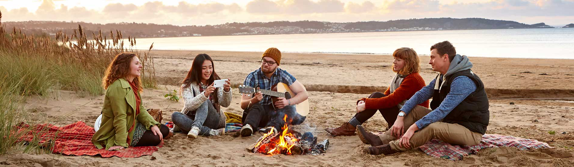 a group of students sitting round a camp fire on a gower beach