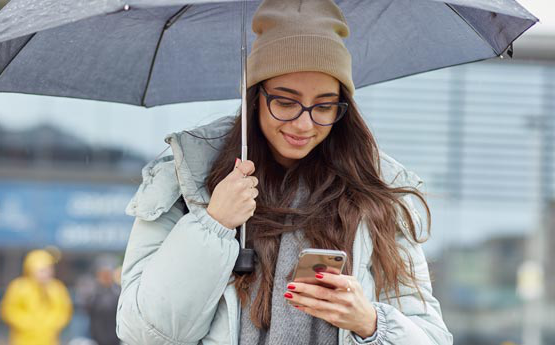 Girl holding an umbrella and looking at her phone.