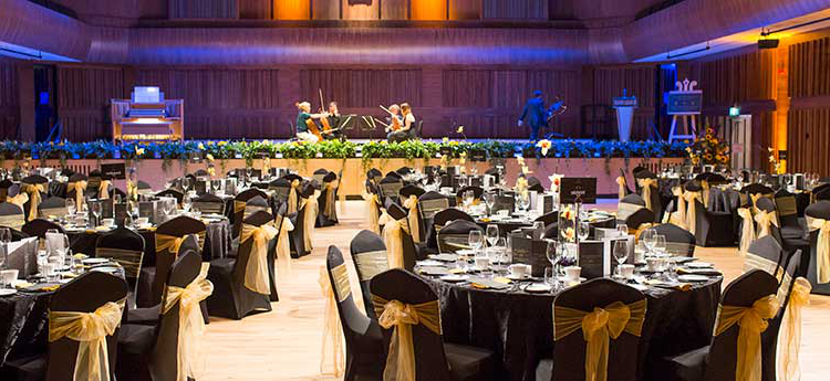 A string quartet practising on the stage with the auditorium prepared ready for a banquet
