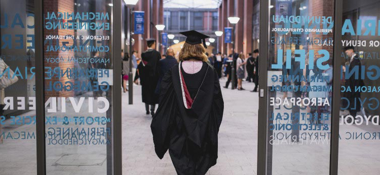 Student walking through engineering building in graduation gown.