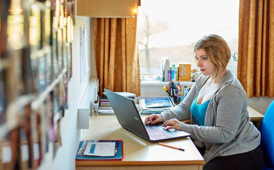 A student sat at her laptop at a desk in student residence