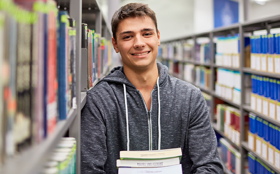 male student in library holding books