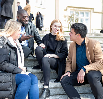 students sitting on steps talking
