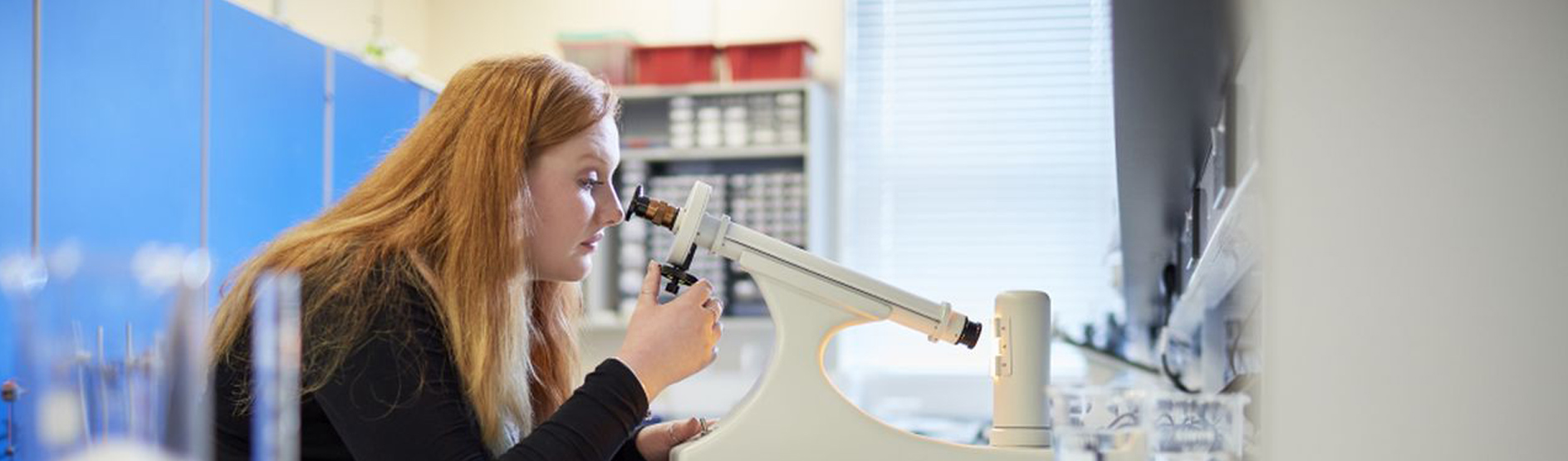 物理 female student with microscope in Lab