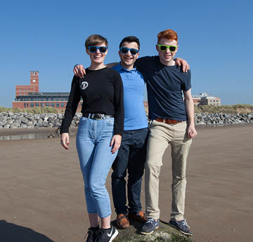 three students smiling on the beach