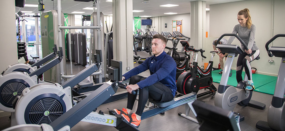 Swansea University Bay Gym. A man is using a rowing machine as a woman rides an exercise bike.