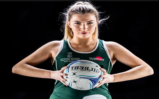 A photo of a netball player posing for a photo holding the ball