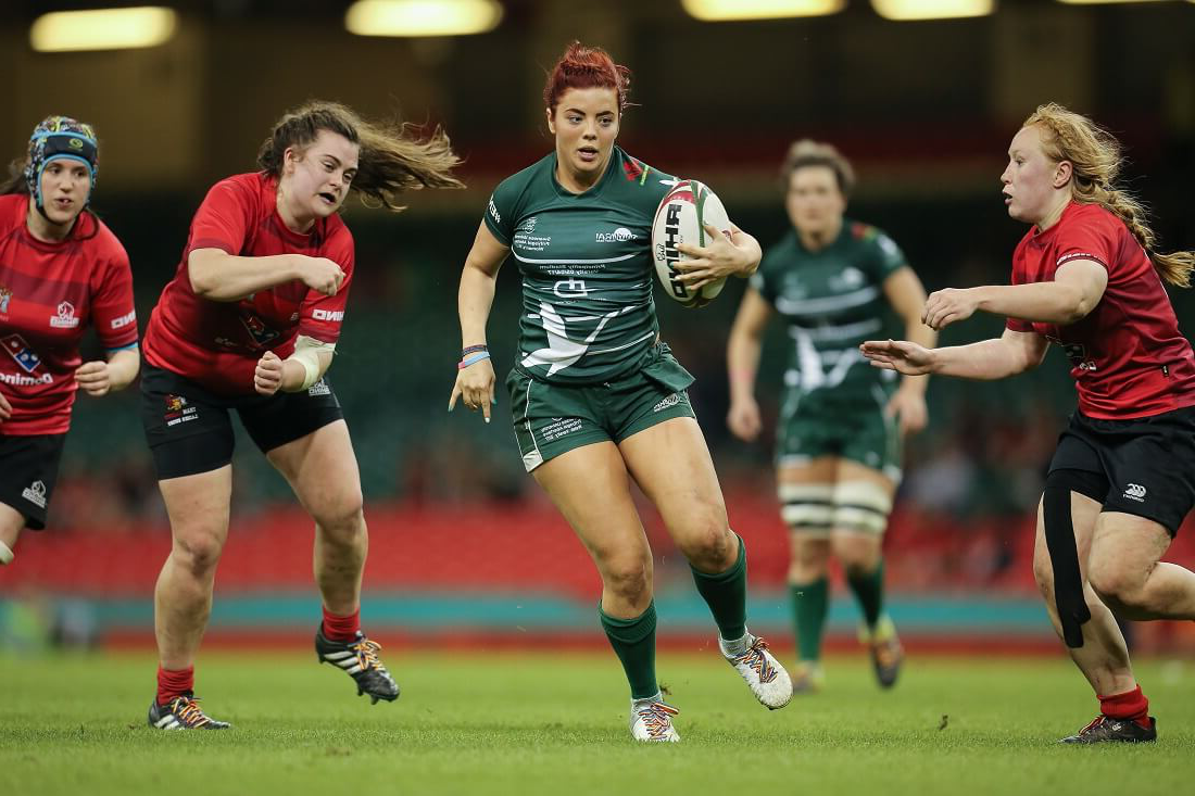 Women's rugby player running with the ball
