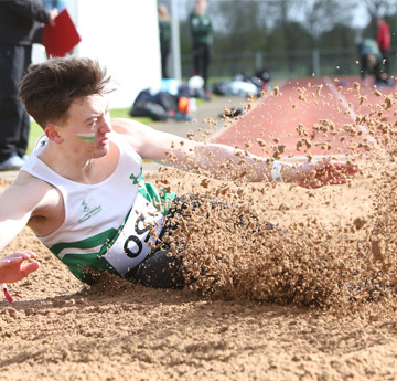 a student competing in the long jump at Varsity