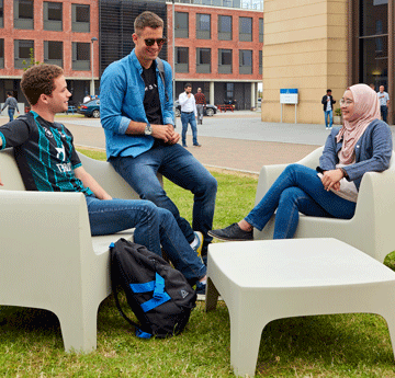 Students sat on chairs outside on Bay Campus