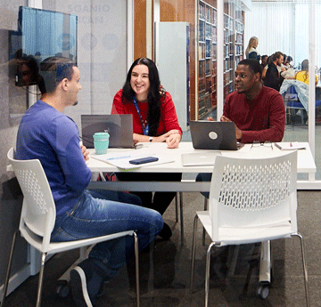 Three students chatting at a desk in a private study room