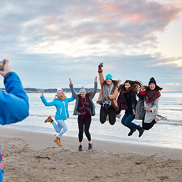 A group of people jumping in the air at the beach. Someone is taking a photo of them. They look very happy.