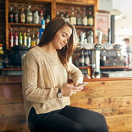 A female staff member sitting at the bar, looking at her phone.