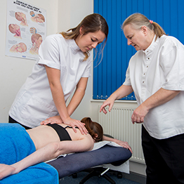 This image shows a student and a staff member giving a staff member a massage.