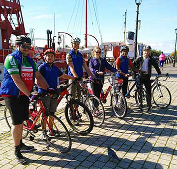 Students and staff members standing next to their bikes in Swansea Marina.