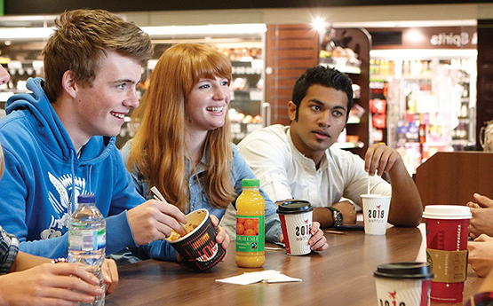 Students socialising around a canteen table.